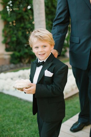 ring-bearer-in-a-black-tuxedo-and-bow-tie-holds-white-rose