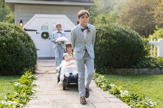 two-ring-bearers-pulling-two-flower-girls-in-blue-wagon-down-aisle-outdoor-wedding