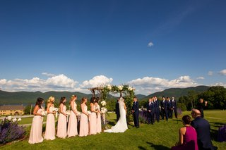 couple-marrying-wedding-party-wooden-arch-outdoors-vermont-mountains