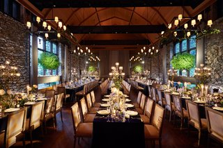wedding-reception-farm-stone-walls-chandeliers-greenery-wood-chairs-long-tables-intimate-seating