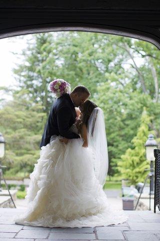 bride-in-strapless-lazaro-dress-with-full-ruffled-skirt-veil-kisses-groom-in-black-tuxedo
