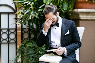 groom-in-tuxedo-getting-emotional-hand-on-eyes-face-while-reading-love-letter-from-bride