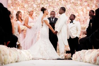 wedding-ceremony-of-megan-wollover-and-tracy-morgan-in-front-of-pink-flower-wall-in-new-jersey