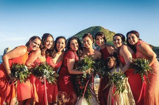 a-bride-in-her-white-wedding-gown-standing-with-her-bridesmaids-wearing-varying-coral-dresses
