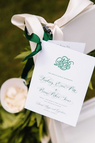 wedding-ceremony-program-green-monogram-and-calligraphy-on-white-chair-with-toss-flower-petals