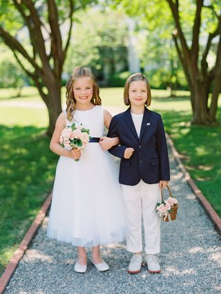 wedding-ceremony-two-flower-girls-one-in-dress-and-one-in-blazer-and-slacks-basket-pink-flowers