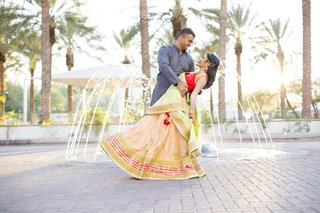 south-asian-wedding-inspiration-bride-in-lehenga-groom-dips-bride-in-front-of-fountain