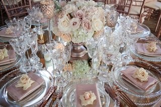 mirror-wedding-table-with-low-centerpiece-candleholders-pink-napkins-fresh-pink-rose-at-each-seat