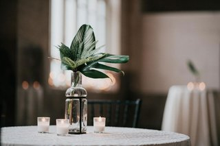 wedding-reception-white-candle-votive-unique-glass-vase-with-greenery-leaves-tropical-jungle-plants