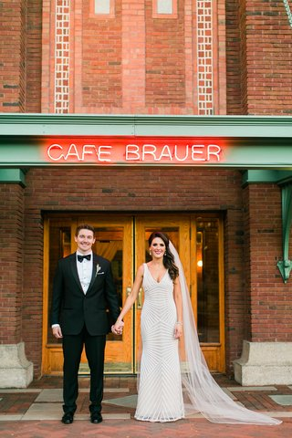 bride-and-groom-hold-hands-couples-portrait-in-front-of-cafe-brauer-chicago-wedding-venue