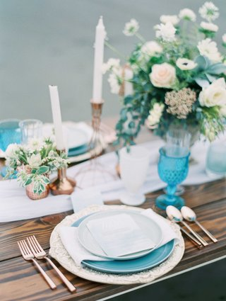 blue-white-green-and-rose-gold-tablescape-on-top-of-a-wooden-table-with-low-lush-floral-arrangement