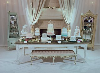nine-wedding-cakes-on-table-in-front-of-fireplace