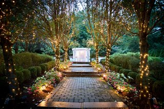 ashley-alexiss-wedding-ceremony-site-outdoor-venue-lights-on-trees-pathway-to-archway-arbor