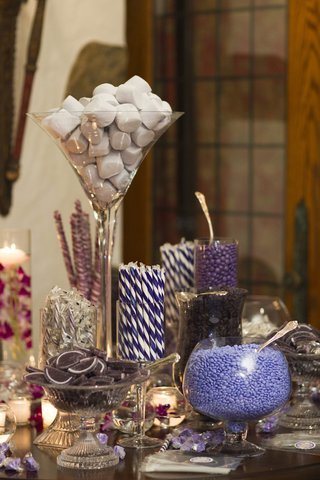 wedding-reception-with-a-candy-bar-offering-different-sweets-in-purple-colors
