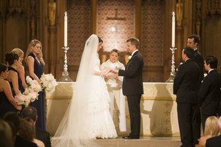 bride-and-groom-exchange-wedding-rings-at-altar