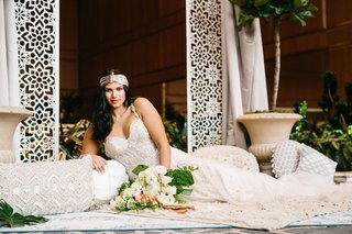 wedding-with-laser-cut-arch-bride-with-headband-and-low-cut-wedding-dress-on-layered-rugs-pillows