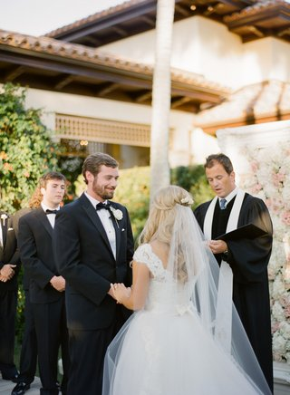 bride-in-a-monique-lhuillier-gown-and-groom-in-a-black-tuxedo-at-a-garden-ceremony