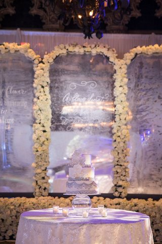 wedding-cake-on-cake-table-silver-white-in-front-of-flower-wall-mirror-quote-etched-white-flowers