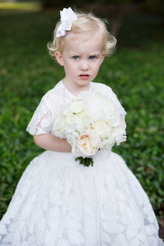 flower-girl-with-blonde-hair-with-white-bow-white-bouquet-and-white-short-sleeve-ball-gown-with-leaf