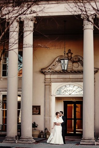 bride-and-groom-in-front-of-marble-columns-of-the-biltmore-ballrooms