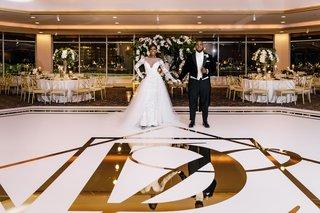 wedding-reception-portrait-of-bride-and-groom-gold-foil-dance-floor-tables-perimeter-ballroom