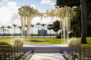 acrylic-wedding-ceremony-arch-white-orchid-and-cascading-flowers-rose-hydrangea-arrangements-candles