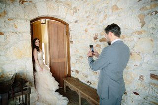 groom-in-grey-suit-takes-photo-on-his-phone-of-the-bride-in-a-ruffled-blush-wedding-dress