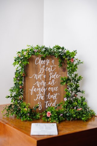white-calligraphy-on-wood-sign-with-green-garlands