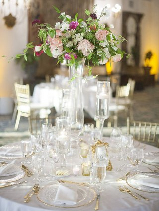 wedding-reception-round-table-gold-flatware-and-charger-plate-tall-centerpiece-in-glass-vase-candles