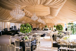 wedding-reception-tent-gold-fabric-chandeliers-black-linens-green-centerpieces-gold-chairs