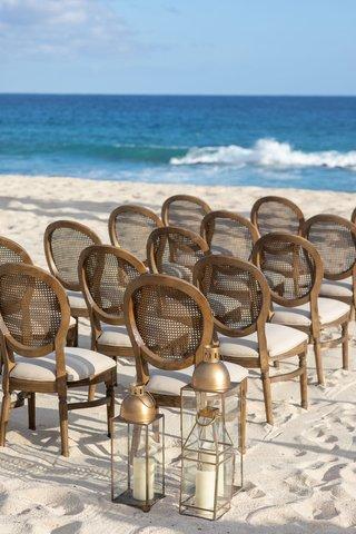 beach-wedding-ceremony-decor-round-back-wood-cane-chairs-white-cushions-gold-lantern-white-sand