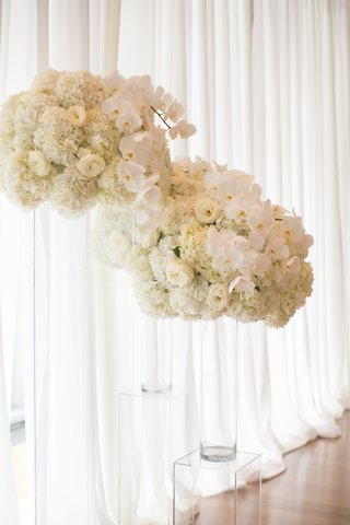 wedding ceremony white drapery white orchid hydrangea rose flowers in vases on acrylic risers