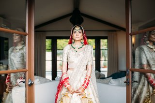 bride in traditional ensemble indian sikh wedding ceremony green jewelry red veil and bangles