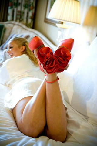 bold-red-pumps-with-red-fabric-flower-and-ankle-strap