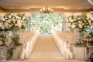 wedding ceremony ballroom white flowers greenery candles lining aisle flower wall backdrop