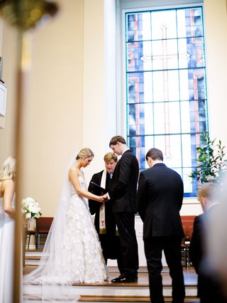 bride in mira zwillinger strapless wedding dress groom with pastor at christian church ceremony stained glass