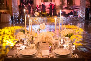 bride-and-grooms-head-table-sweetheart-table-with-candles-plates-skull-dancefloor-lit-in-background