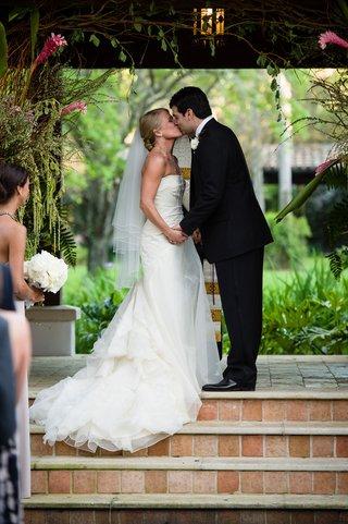 bride-and-groom-kissing-on-brick-tile-steps