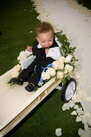 young-ring-bearer-in-white-wagon-at-wedding-ceremony