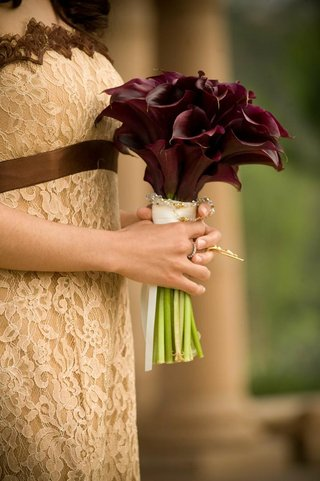 bridesmaid-holding-bouquet-of-burgundy-calla-lilies