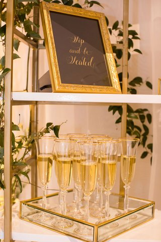 wedding reception bar gold white bookcase with glass tray champagne flutes black gold sign sip and be seated