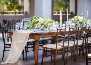 wedding-reception-long-wood-table-with-wood-chairs-fabric-runner-sheer-gold-taper-candles-yellow