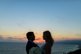 almost-silhouette-of-bride-and-groom-framing-sunset-over-the-ocean