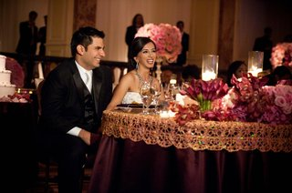 newlyweds-sitting-at-plum-and-gold-table