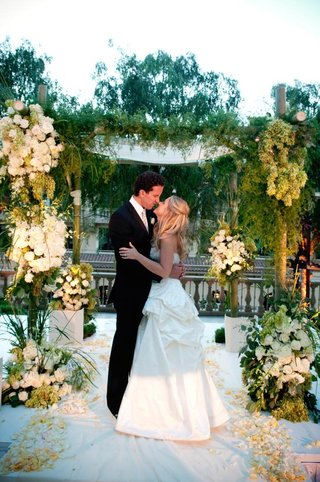 bride-and-groom-eskimo-kiss-under-green-and-white-flower-arch