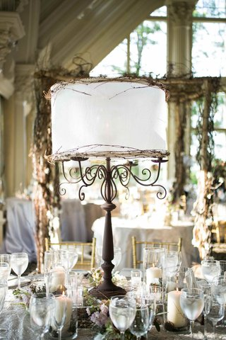 iron-candelabra-centerpiece-with-white-lamp-shade-and-branches