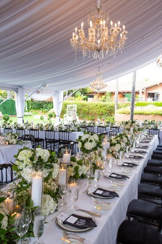 wedding reception long white table black monogram napkins hydrangea pillar candles chandelier tent