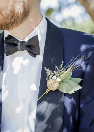close-up-picture-of-grooms-navy-blue-tuxedo-and-his-wheat-boutonniere-with-green-leaves-wildflowers