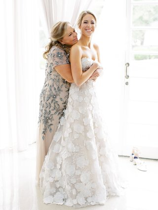 bride in mira zwillinger flower applique wedding dress mother hugging from behind short sleeve blue beaded embroidery