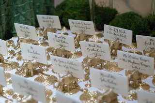 white-escort-cards-with-black-calligraphy-on-small-golden-elephant-figurines